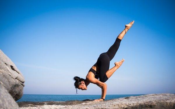 崖でヨガポーズをする女性