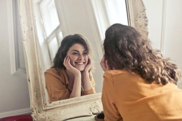 鏡を見て笑顔を作る女性
