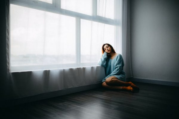 窓辺で憂鬱になっている女性