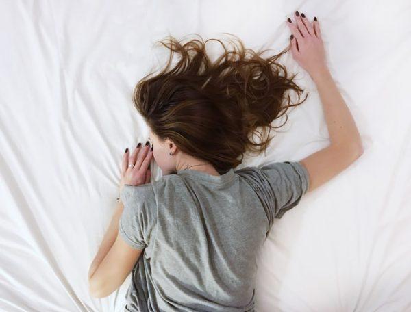 ベッドに倒れこむ女性