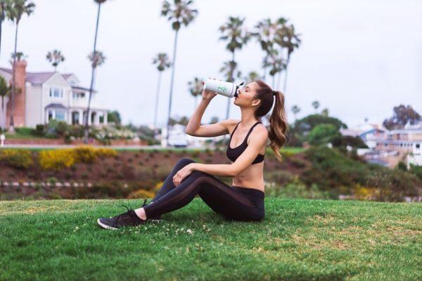 外でスポーツドリンクを飲む女性