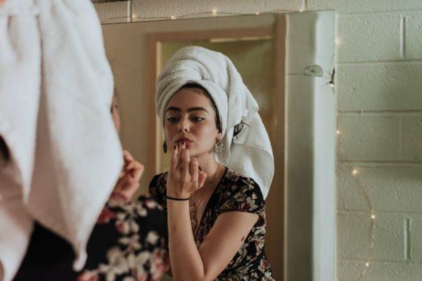 鏡を見てメイクをする女性