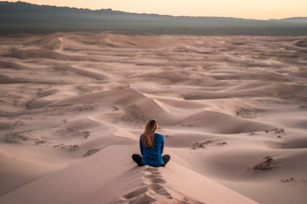 砂漠でヨガをする女性