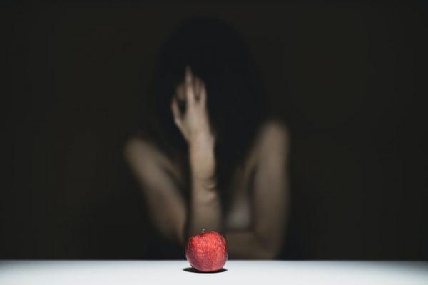りんごを目の前に苦しむ女性