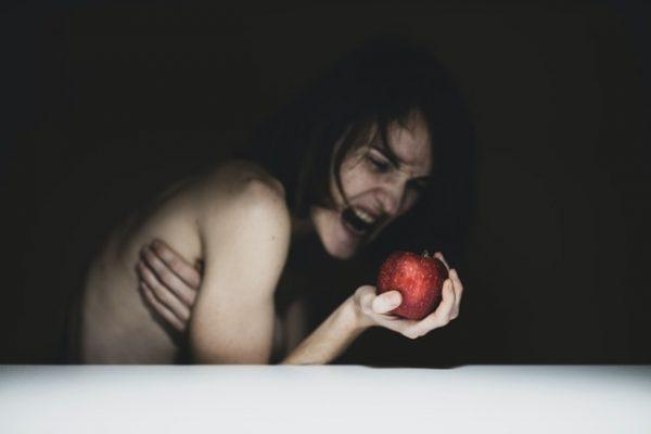 りんごを手に苦しむ女性