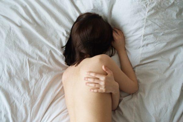 女性の背中 ベッド